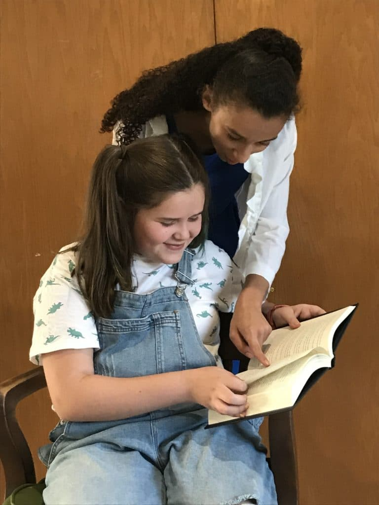 Miss Honey (Kenzie Losinski) helps Matilda (Ella Taylor) with her newest novel.